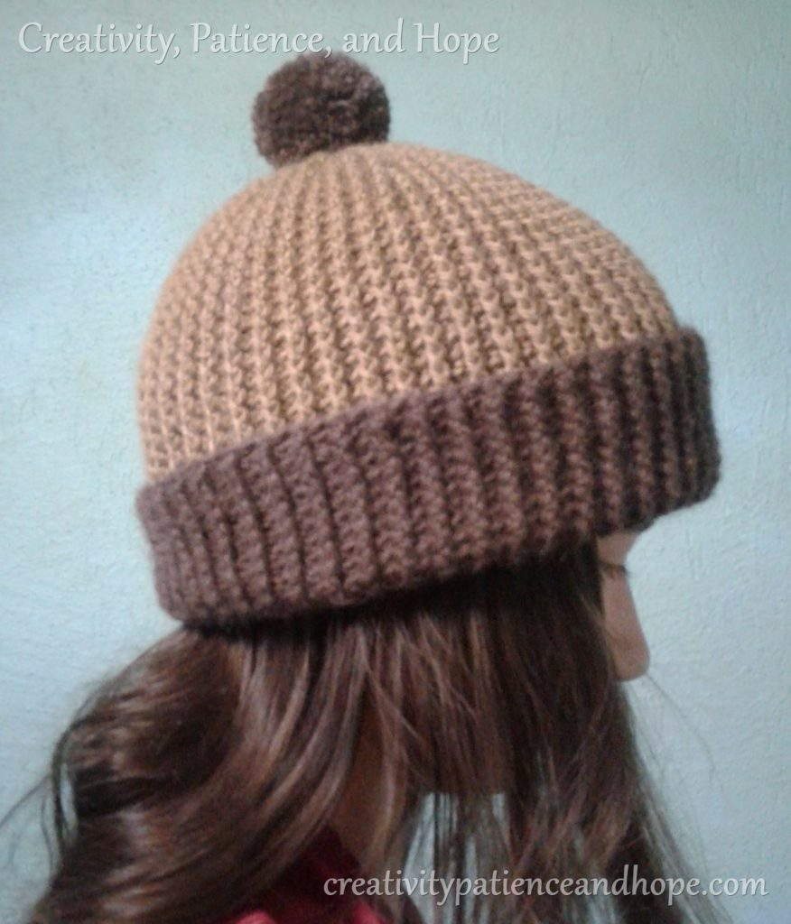 girl wearing brown crochet hat with dark brown trim and pompom