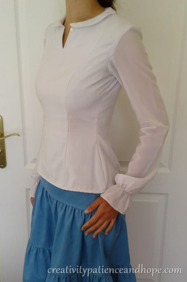 side front view of white fitted blouse with princess seams and long sleeves