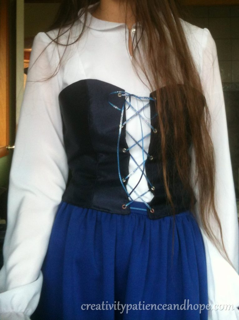 navy blue corset over long-sleeved white fitted blouse and blue skirt