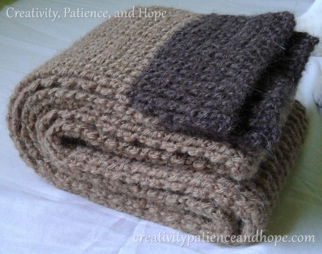 folded brown crochet scarf with dark brown trim