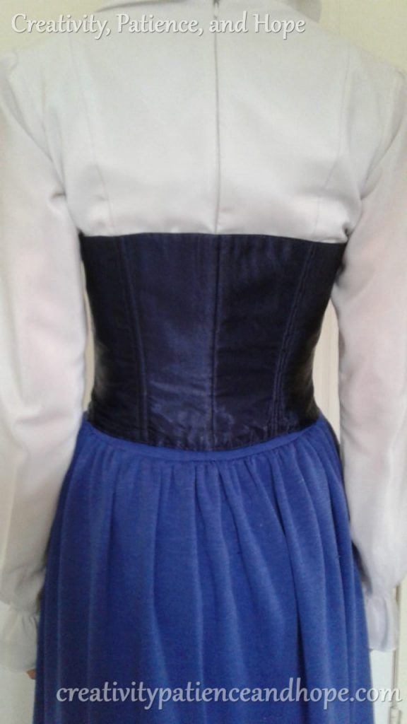 back view of navy blue corset over white long-sleeved blouse